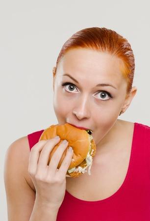 Woman eating hamburger Stock Photo - 13397158