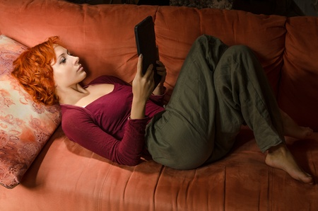 ebook: Curly woman on a sofa with ebook