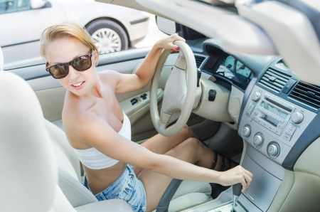 cabrio: Woman driving on a parking lot