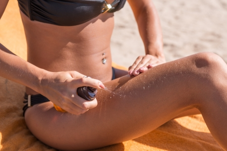 Sensous slim woman applying suntan oil photo