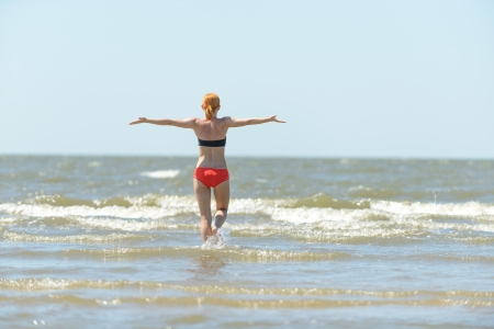 Slim young woman running into sea waves photo
