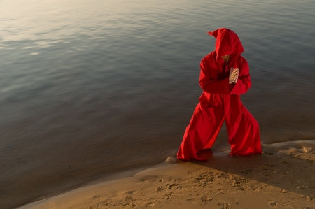 gung: Karate monk wearing red hood meditating Stock Photo