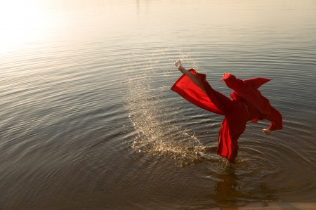 Karate monk wearing red hood kicking photo