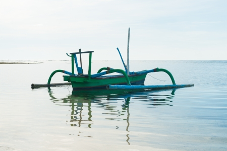 Outrigger boat with reflection photo