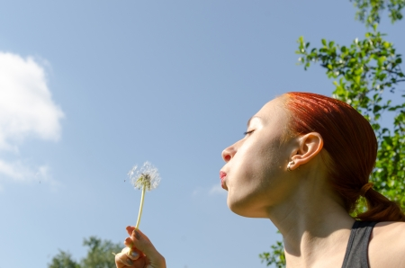 Young woman blowing dandelion photo