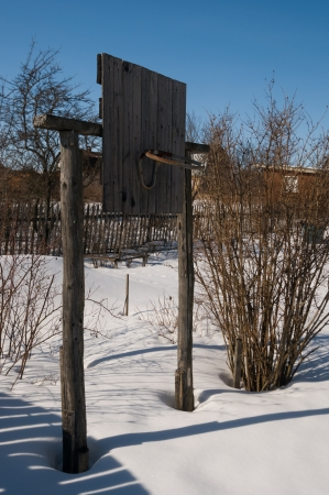 Basketball hoop made of wood standing in snow photo