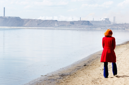 Young woman walks alone on a beach heading towards industrial landscape photo