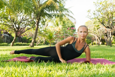 comely: Young woman doing yoga exercises in the lush tropical garden