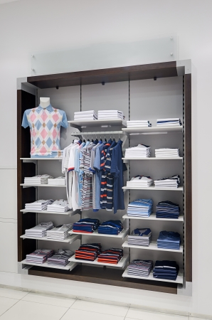 Various color clothes at shelf in shop photo