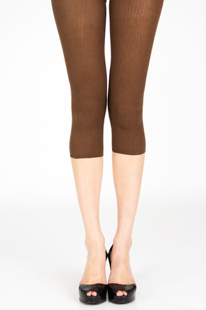 bashfulness: Long Slim legs wearing colorful leggins on plain background Stock Photo