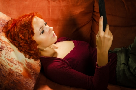 Young woman on a couch interacting with tablet pc or e-reader photo