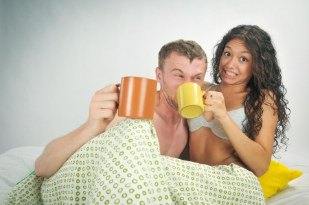 Young caucasian heterosexual couple in bed holding coffee mugs photo
