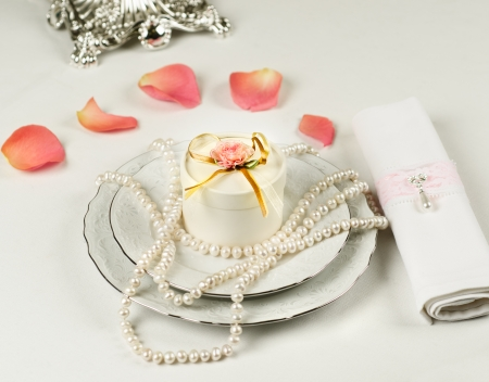 Wedding table accessories with rose petals and pearls photo