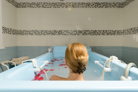 Young woman taking bath with milk and rose petals at spa salon Stock Photo - 22609498