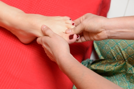 Young woman enjoying traditional thai foot massage