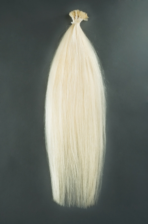 uncombed: Blond hair extensions shot on a dark background