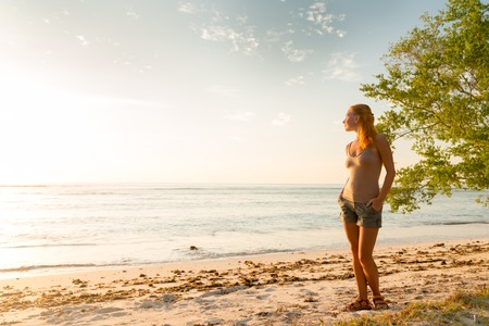 raises: Young woman watching as sun sets over Pacific Ocean Stock Photo