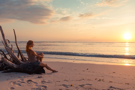 Young woman watching as sun sets over Pacific Ocean photo