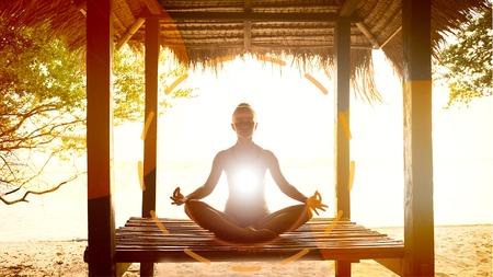 Young woman meditating in lotus pose at the ocean shore