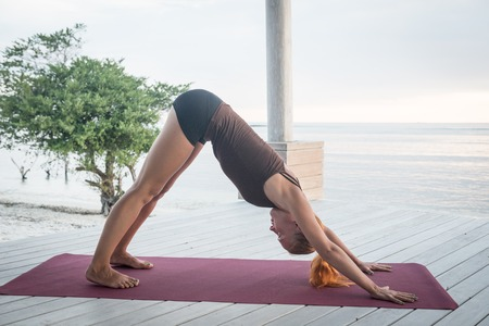 Young slim lady doing yoga downward facing dog on a beach with sunset over Bali in the background photo