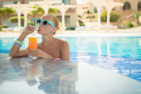 pool bars: Girl in pool bar at tropical tourist resort vacation destination Stock Photo