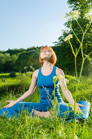 Woman doing yoga asana outdoors in the nature photo