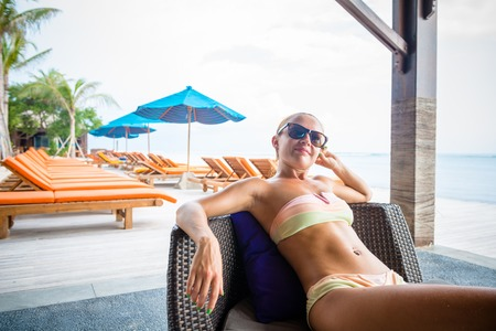Young woman relaxing at the beach bar in Indonesia photo