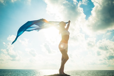free standing: Freedom and beauty concept. Beautiful girl with blue scarf standing on the Rock. Flying. Free. Vacation