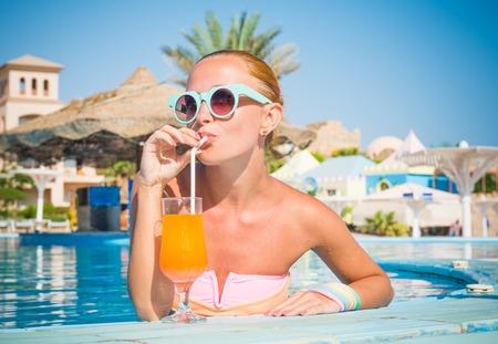 Girl in pool bar at tropical tourist resort vacation destination Stok Fotoğraf