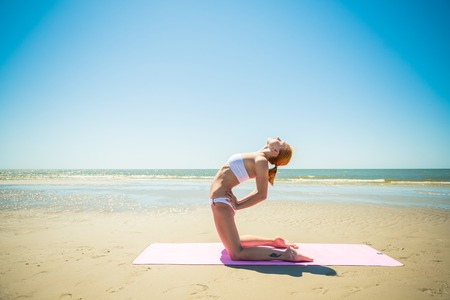 Woman doing yoga asana at the beach photo
