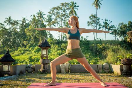 sfondo giungla: Giovane donna che svolgono yoga asana al tramonto con sfondo della giungla Archivio Fotografico