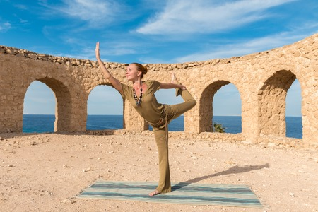 ancient yoga: Woman doing yoga asana at exotic ancient location Stock Photo