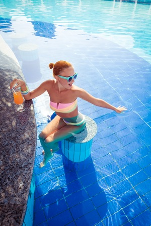 pool party: Girl in pool bar at tropical tourist resort vacation destination Stock Photo