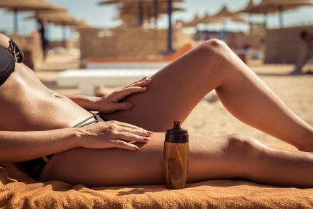 Sinnliche schlanke Frau Anwendung Sonnencreme Öl, ihren Körper am Strand