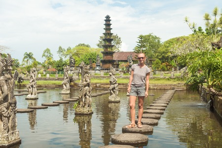 Happy tourist at Tirtagangga water palace with fountains  and ponds on Bali, Indonesia photo