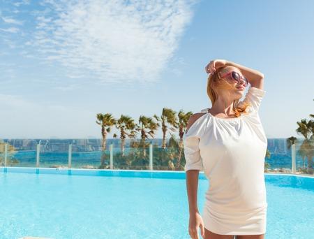 Young woman enjoying sun by pool at tourist resort photo