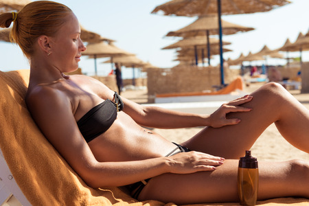 Sensuous slim woman applying suntan lotion oil to her body at the beach Stock Photo