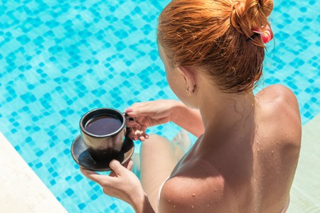 Young woman wearing swimsuit enjoying coffee near swimming pool at exotic location photo