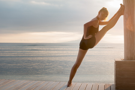 Young slim lady doing yoga stretching exercises on a beach with sunset over Bali in the background photo