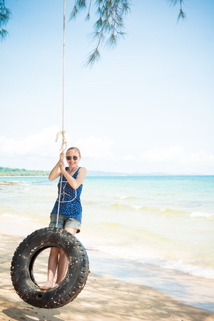 russian ethnicity caucasian: Happy woman having fun on tire swing at the beach. Phu Quoc, Vietnam