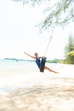 russian ethnicity: Happy woman having fun on tire swing at the beach. Phu Quoc, Vietnam