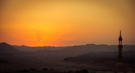 foreground focus: Sunset over desert with muslim mosque in the foreground. Focus on distant mountains