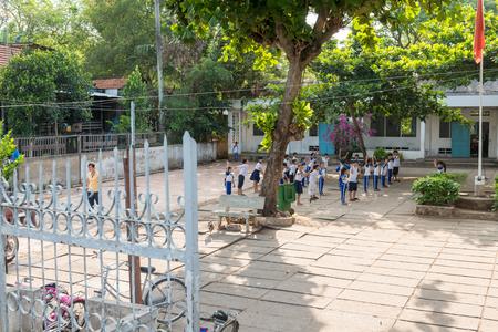 school yard: LONG XUYEN, VIETNAM - April 26, 2014 - Children perform physical exercises at local school yard
