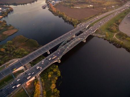 car lots: Bridge with lots of car traffic over the river at sunset Stock Photo