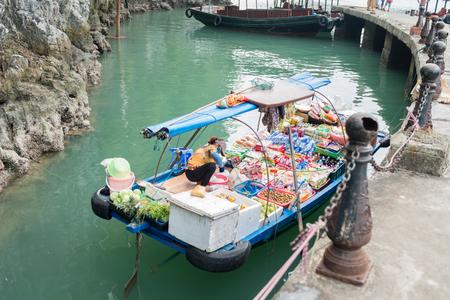 halong: HALONG, VIETNAM - May 8, 2014 - Floating vendor selling various fruits and snacks to tourists visiting Halong
