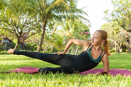 russian ethnicity caucasian: Young woman doing yoga exercises in the lush tropical garden