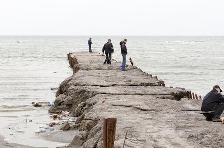 azov sea: MARIUPOL, UKRAINE - April 18, 2012 - People fishing at local pier in Mariupol at Azov sea