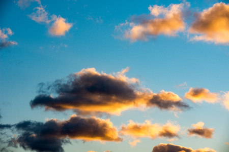 Puffy and colorful sunset clouds closeup over blue sky Stock Photo
