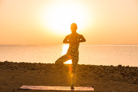 asana: Yoga practice. Woman doing asana at sunrise Stock Photo