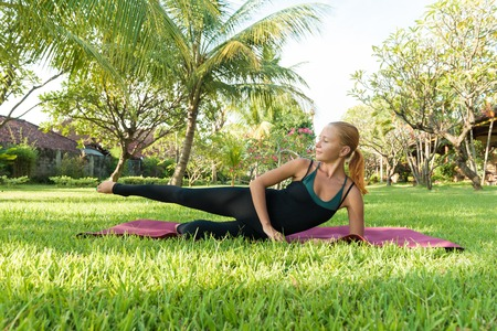 tree position: Woman doing yoga in garden Stock Photo